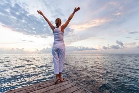 Blanke vrouw het beoefenen van yoga bij kust Stockfoto