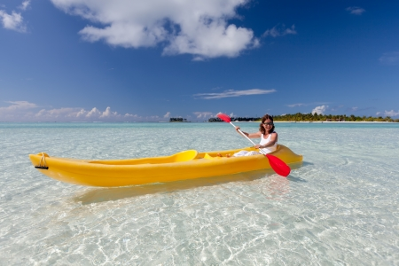 Young caucasian woman kayaking in sea at Maldives  photo