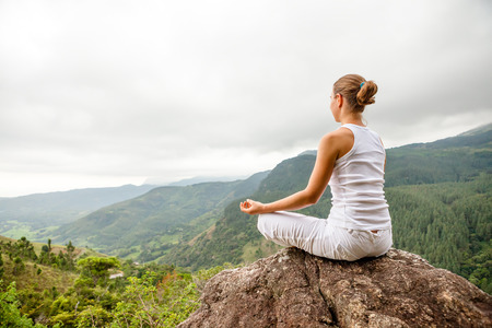Woman is doing yoga exercises in mountains