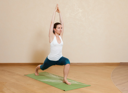 virabhadrasana: Caucasian woman is practicing yoga at studio (virabhadrasana) Stock Photo