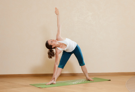 trikonasana: Caucasian woman is practicing yoga at studio (uttkhita trikonasana)