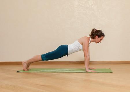 Caucasian woman is practicing yoga at studio (chaturanga dandasana) photo