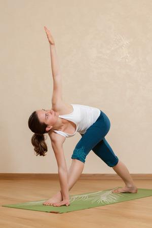 trikonasana: Caucasian woman is practicing yoga at studio (trikonasana)
