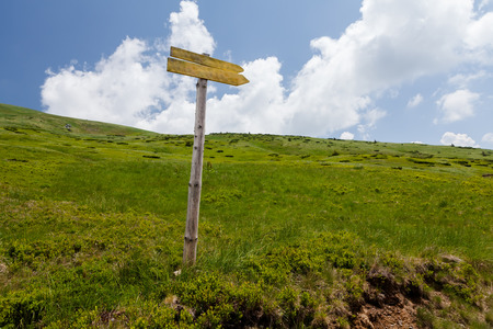 directional arrow: Signpost on trail in front of blue sky