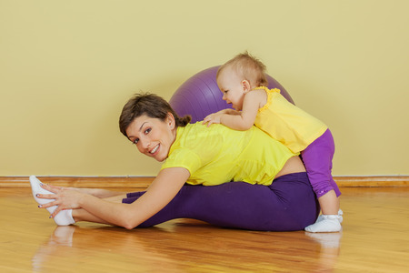 Mother does physical exercises with her daughter at home photo