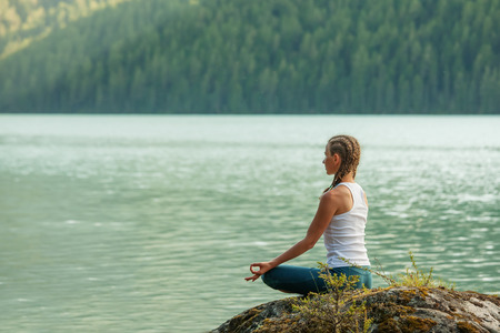 meditating woman: Young woman is practicing yoga at mountain lake