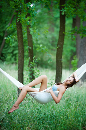 Young woman lying in a hammock on resort photo