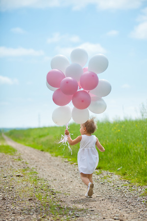 Small caucasian plays in summer park with colorful baloons photo