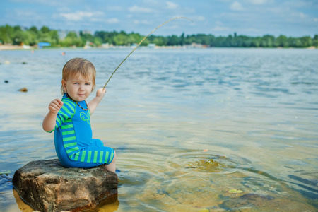 Adorable baby on river with fishing-rod and fishing photo