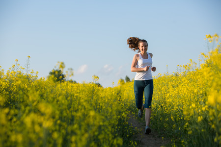 Young woman is jogging in yellow rapeseed field at sunset photo