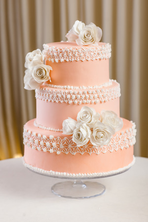 Pink and white wedding cake with individual decoration at withe table  photo