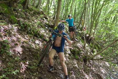 problematic: Man carries mtb bicycle over problematic path in greent forest  Stock Photo