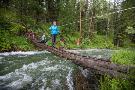 Backpackers are crossing mountain river by wooden log in Altai mountains, Russia photo