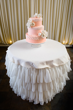 tiered: Pink and white wedding cake on white table