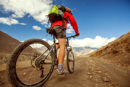 Girl cycling at the road in Himalaya