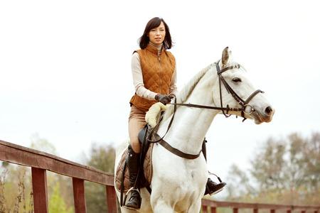 Vrouw jockey rijdt het paard buiten