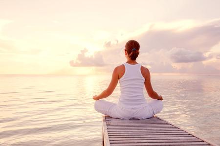 relaxation: Caucasian woman practicing yoga at seashore