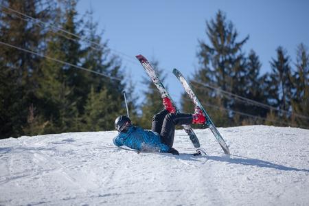 Sciatore caduto durante la discesa dalla montagna Archivio Fotografico - 33472352