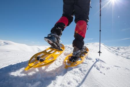 Wandelaar sneeuwschoenen in de winter de bergen tijdens zonnige dag