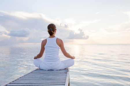 Caucasica donna praticare lo yoga in riva al mare Archivio Fotografico - 33835044