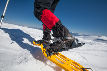 Hiker snowshoeing in winter mountains during sunny day photo