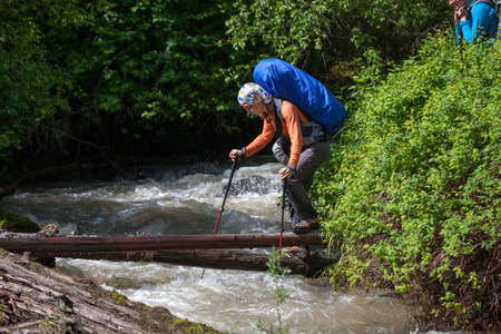 Backpacker is crossing mountain river by wooden log in Altai mountains, Russia photo