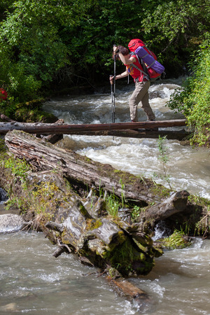 difficult journey: Backpacker is crossing mountain river by wooden log in Altai mountains, Russia Stock Photo