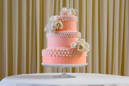 withe: Pink and white wedding cake with individual decoration at withe table Stock Photo