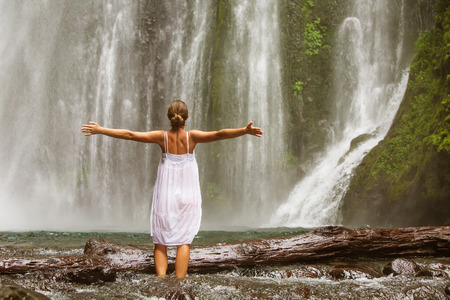 young woman doing yoga in a forest near waterfall Standard-Bild