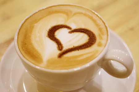 cinnamon swirl: Coffee cup with milk and heart shape