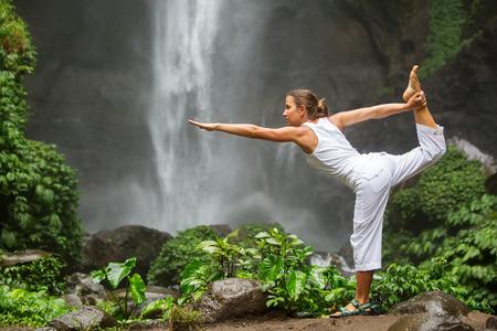 Meditierende Frau, die Yoga zwischen Wasserfällen
