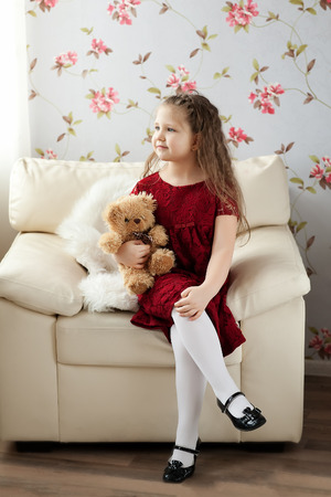 Girl with teddy bear in hand photo