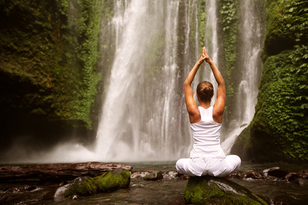 young woman doing yoga in a forest near waterfall Stock Photo