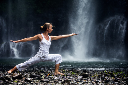 vrouw mediteren doen yoga tussen watervallen Stockfoto