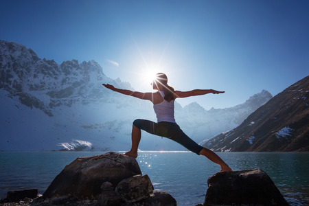 rivers mountains: Young woman is practicing yoga at mountain lake