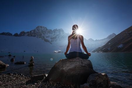 Jonge vrouw oefent yoga bij bergmeer