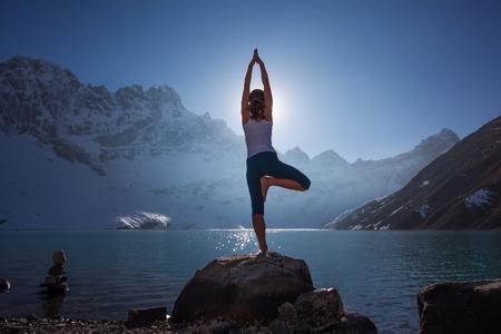 La giovane donna è praticare lo yoga al lago di montagna Archivio Fotografico - 35746958