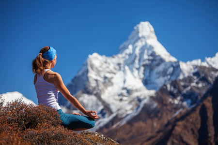 yoga rocks: Young woman is practicing yoga against Himalaya mountains