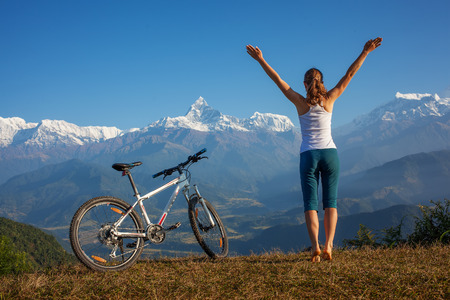 mind: woman practicing yoga, relaxing after riding bikes high in mountain