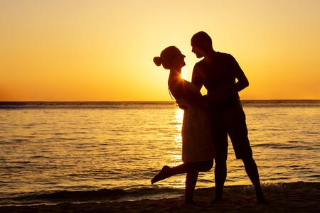 beach wedding: Romantic couple on the beach at colorful sunset on background