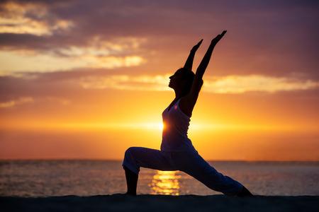 yoga sunset: Caucasian woman practicing yoga at seashore