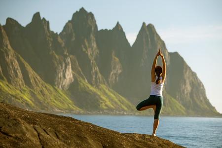 젊은 여자는 노르웨이 산 사이 요가 연습한다