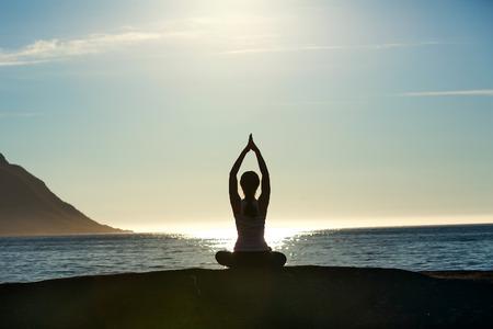 Jonge vrouw is het beoefenen van yoga tussen de bergen in Noorwegen