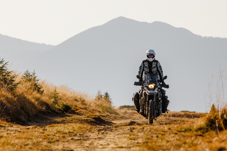 Motorbiker travelling in autumn mountains Standard-Bild