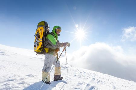 backpacker: Backpacker man is posing in winter mountains