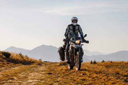 dirt: Motorbiker travelling in autumn mountains Stock Photo