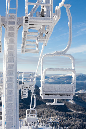 sports and recreation: Frozen chair lift at snow resort in winter mountains on sunny day