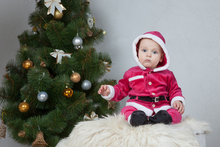santa suit: Small boy in Santa suit plays near new-year tree in white studio