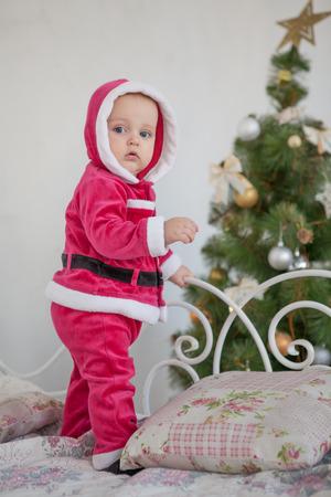 santa suit: Small boy in Santa suit plays in white studio