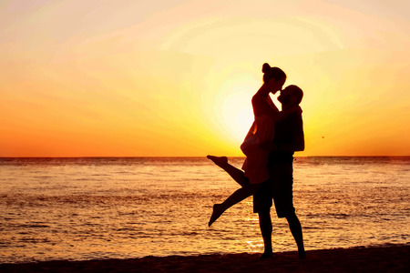 Romantic couple on the beach at colorful sunset on background 版權商用圖片 - 54040820